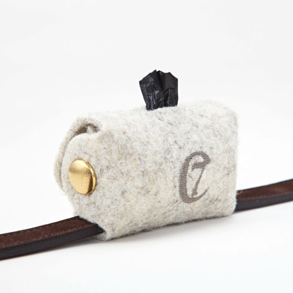 Bajspåsehållare i filt med guldiga knappar sitter fastknäppt på ett hundkoppel i brunt läder
