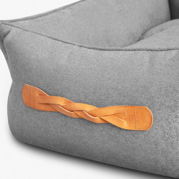 Sidan av en ljusgrå hundbädd. Sidan är försedd med ett flätat handtag i cognacsfärgat läder