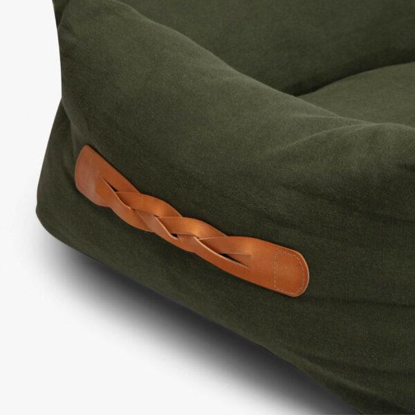 Läderdetalj i form av ett flätat handtag på kortsidan av en rektangulär grön hundbädd