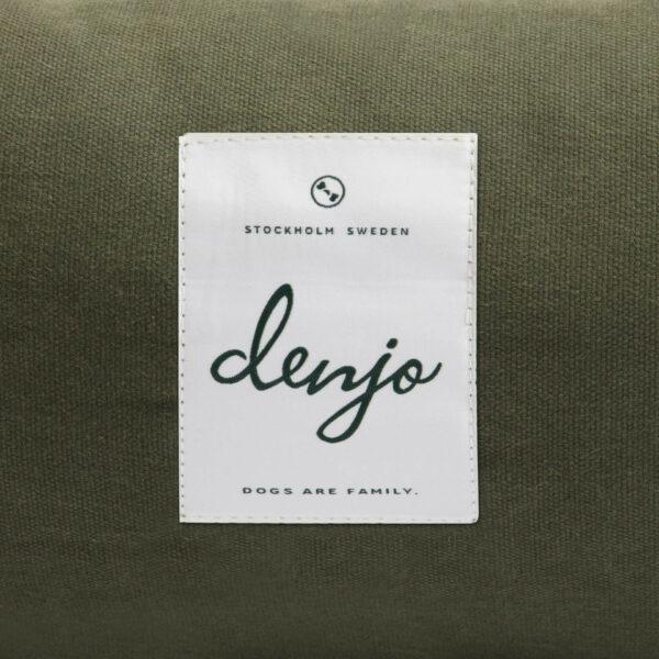 Textiletikett framtill på en hundbädd. På textiletiketten står det Denjo i grön text