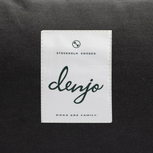 Vit och grön textiletikett med texten Denjo ör placerad på en mörkgrå hundbädd
