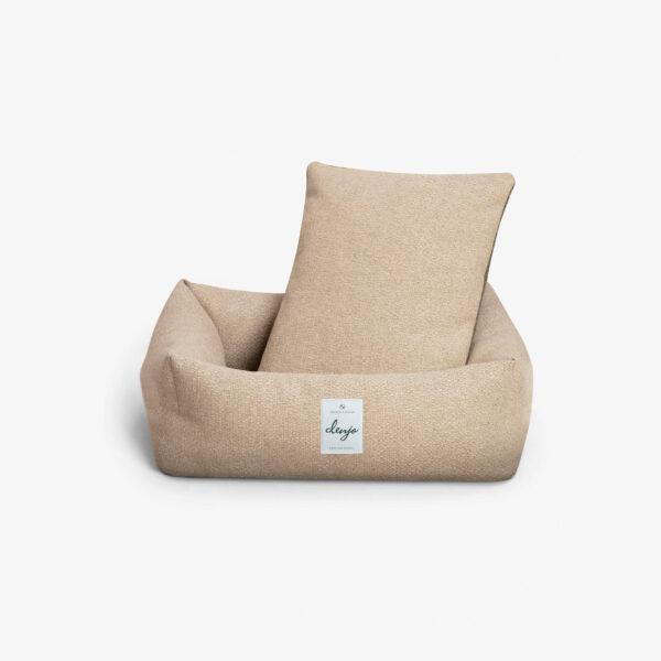 Rektangulär hundbädd med textiletikett framtill. I hundbädden står en rektangulär kudde i samma textil.