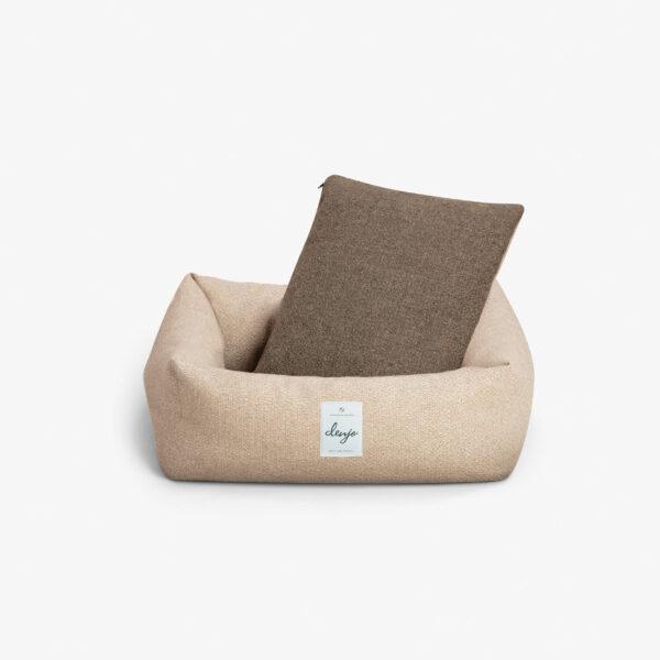 Rektangulär hundbädd med textiletikett framtill. I hundbädden står en mörkbrun kudde.