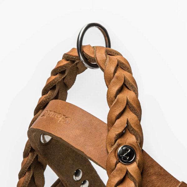 Flätade detaljer av läder på en hundsele