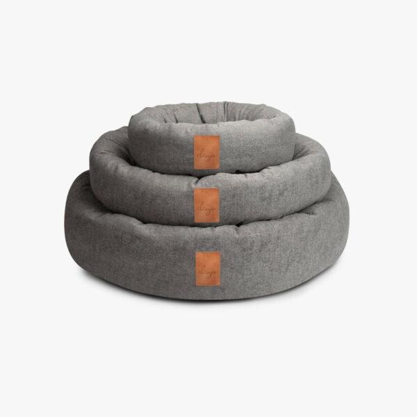 Tre ljusgrå runda hundbäddar med läderdetalj framtill, står staplade på varandra